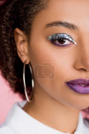 Photo pour Afrique américaine fille avec argent paillettes fards à paupières et pourpre lèvres, isolé sur rose - image libre de droit