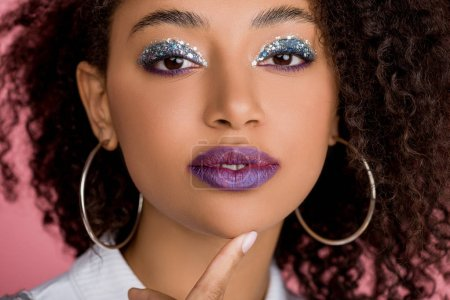 attractive african american girl with silver glitter eyeshadows and purple lips, isolated on pink