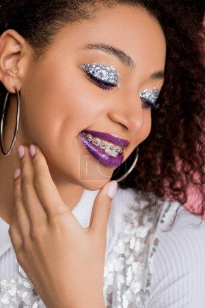 Photo pour Joyeuse fille afro-américaine avec des fards à paupières à paillettes argentées et des lèvres violettes portant une robe paillettes, isolée sur rose - image libre de droit