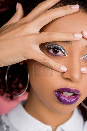 Photo pour Jolie fille afro-américaine avec des fards à paupières à paillettes argentées et des lèvres violettes, isolée sur rose - image libre de droit