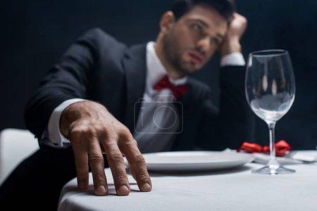 Photo pour Foyer sélectif de l'homme élégant avec la main par la tête assis à la table servie isolé sur noir - image libre de droit
