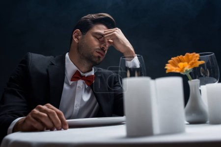 Selective focus of tired man sitting at served table isolated on black