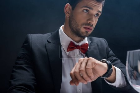 Photo for Selective focus of handsome man in suit waiting at table with wine glass isolated on black - Royalty Free Image