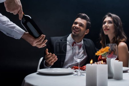 Photo for Selective focus of waiter showing wine bottle to elegant couple at served table isolated on black - Royalty Free Image