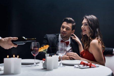 Kellner schenkt Wein in Glas mit Eleganz Paar am Tisch serviert isoliert auf schwarz