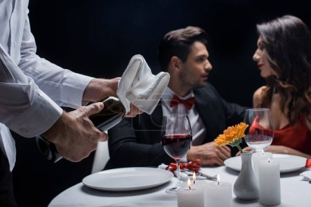 Photo for Selective focus of waiter with wine bottle and towel and elegance couple at served table at background isolated on black - Royalty Free Image