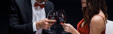 Photo pour Vue panoramique d'élégance couple cliquetis avec des verres à vin isolés sur noir - image libre de droit