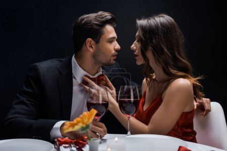 Photo for Side view of beautiful woman adjusting bow tie of handsome man during romantic dinner isolated on black - Royalty Free Image