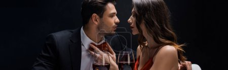 Panoramic shot of attractive woman adjusting bow tie of elegant man by wine glasses isolated on black