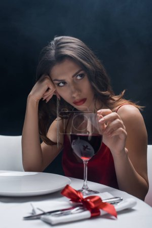 Photo for Attractive woman with hand by head touching wine glass at served table on black background with smoke - Royalty Free Image