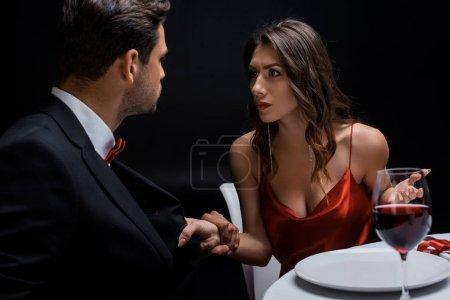 Eleganz Paar schaut einander an, während es sich am Tisch streitet, isoliert auf schwarz