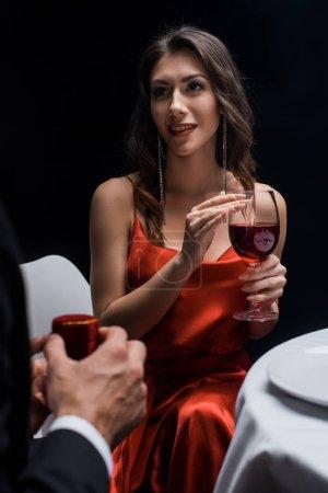 Photo pour Concentration sélective de la femme élégante avec verre à vin en regardant petit ami avec boîte à bijoux isolé sur noir - image libre de droit