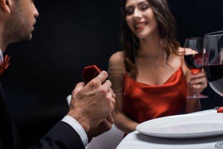 selektiver Fokus des Mannes präsentiert Schmuckschatulle bei lächelnder Freundin mit Weinglas beim romantischen Abendessen isoliert auf schwarz