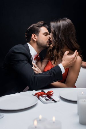 Photo pour Selective focus of elegant couple kissing during romantic dinner isolated on black - image libre de droit