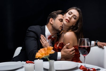Photo for Handsome man kissing beautiful girlfriend during romantic dinner isolated on black - Royalty Free Image