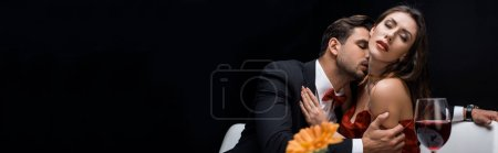 Photo for Panoramic shot of handsome man kissing elegant woman by wine glass isolated on black - Royalty Free Image