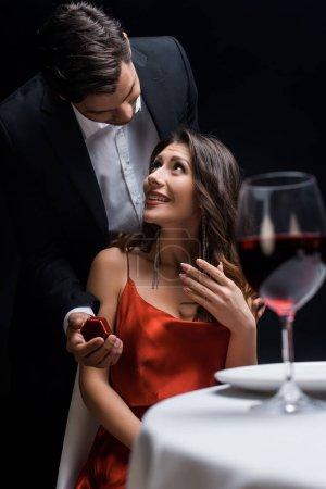 Photo pour Foyer sélectif de l'homme élégant présentant boîte avec des bijoux à la petite amie souriante à la table servie isolé sur noir - image libre de droit