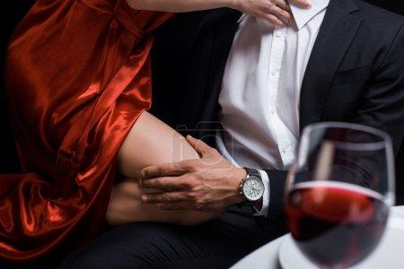 Photo pour Vue croustillante d'un homme tenant par le genou une femme élégante au cours d'un dîner romantique isolé sur un noir - image libre de droit