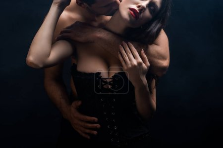 Photo pour Shirtless man hugging and kissing sexy girlfriend in corset isolated on black - image libre de droit