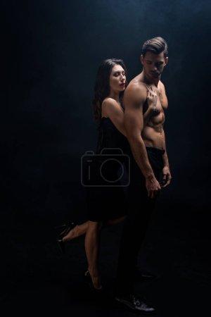 Photo pour Pleine longueur de belle femme étreignant torse nu copain isolé sur noir - image libre de droit