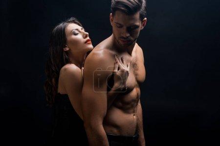 Photo pour Vue latérale de belle femme étreignant petit ami musclé isolé sur noir - image libre de droit
