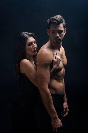 Photo pour Vue latérale de la fille attrayante touchant homme torse nu isolé sur noir - image libre de droit