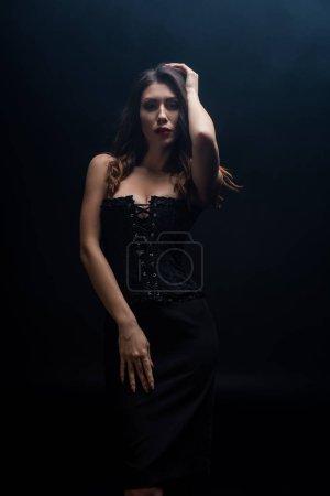 Photo pour Femme sensuelle dans le corset regardant la caméra isolée sur noir - image libre de droit