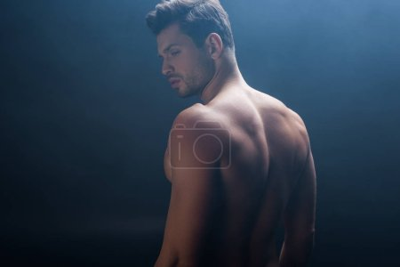 Photo for Handsome muscular man looking away on black background with smoke - Royalty Free Image