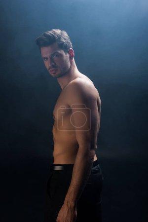 Photo pour Vue latérale de l'homme torse nu regardant la caméra sur fond noir avec de la fumée - image libre de droit