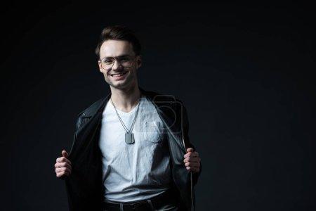 Foto de Sonriente hombre brutal con estilo con las manos en camisa de biker aislada sobre negro. - Imagen libre de derechos