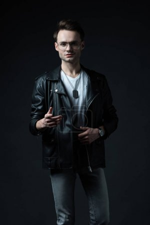Photo for Stylish brutal man in biker jacket gesturing isolated on black - Royalty Free Image