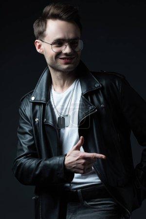 Foto de Sonriente hombre brutal con estilo en la chaqueta de los moteros señalando con el dedo aislado en negro. - Imagen libre de derechos