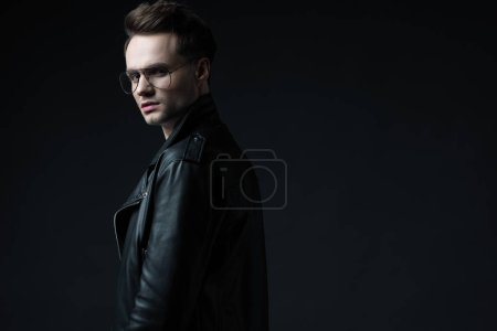 Photo for Side view of stylish brutal man in biker jacket looking at camera isolated on black - Royalty Free Image