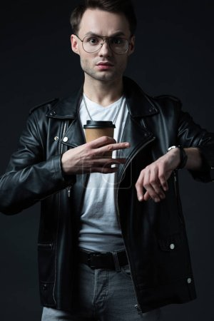stressed stylish brutal man in biker jacket with wristwatch and coffee to go isolated on black