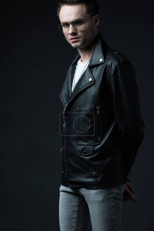 Photo for Serious stylish brutal man in biker jacket with hands behind back isolated on black - Royalty Free Image