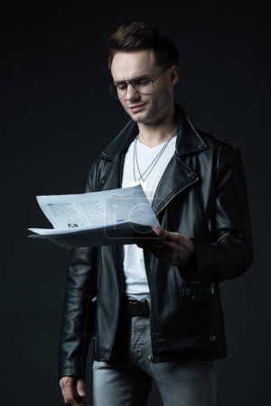 Foto de Sonriente hombre brutal con estilo en la chaqueta de los motoristas, con un periódico aislado en negro. - Imagen libre de derechos