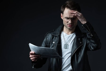 Photo for Worried stylish brutal man in biker jacket with newspaper isolated on black - Royalty Free Image