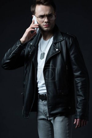 Photo for Tense stylish man in leather jacket talking on smartphone isolated on black - Royalty Free Image