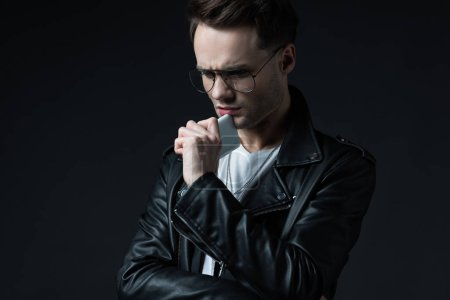 Photo for Worried stylish man in leather jacket with smartphone isolated on black - Royalty Free Image