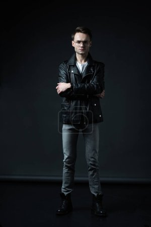 Photo for Stylish brutal man posing in biker jacket on black - Royalty Free Image
