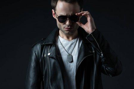 Foto de Elegante hombre brutal que se pone en camisa de biker y gafas de sol aislados en negro. - Imagen libre de derechos
