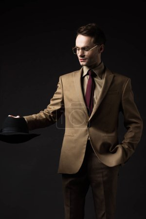 smiling elegant man in beige suit and eyeglasses holding hat isolated on black