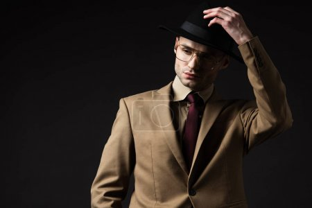 Photo for Elegant man in beige suit and eyeglasses putting on hat isolated on black - Royalty Free Image