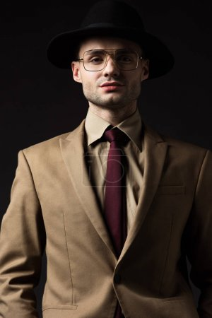 Photo for Confident elegant man in beige suit, hat and eyeglasses isolated on black - Royalty Free Image