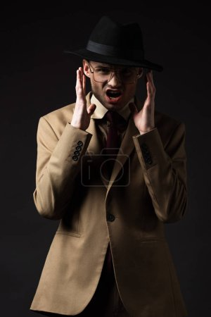 Photo for Mad elegant man in beige suit, hat and eyeglasses isolated on black - Royalty Free Image