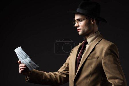 Photo pour Vue latérale de l'homme élégant en costume beige, chapeau et lunettes lecture journal isolé sur noir - image libre de droit