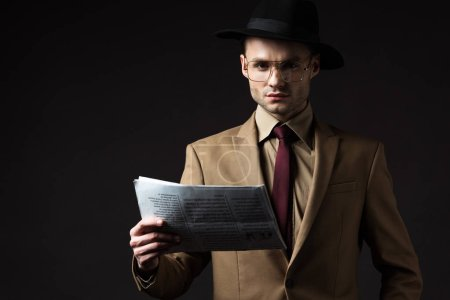 Photo for Serious elegant man in beige suit, hat and eyeglasses holding newspaper isolated on black - Royalty Free Image