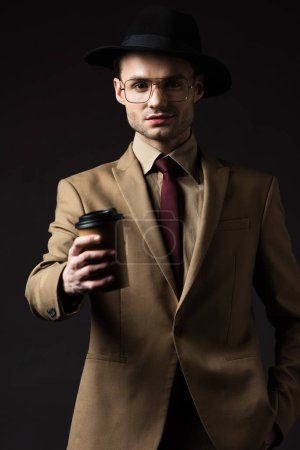 elegant man in beige suit, hat and eyeglasses giving paper cup isolated on black