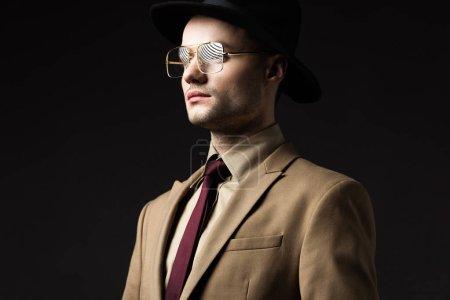elegant man in beige suit, hat and eyeglasses looking away isolated on black