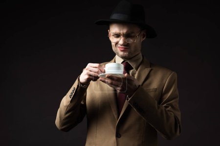 Photo for Skeptical elegant man in beige suit, hat and eyeglasses holding coffee cup and saucer isolated on black - Royalty Free Image